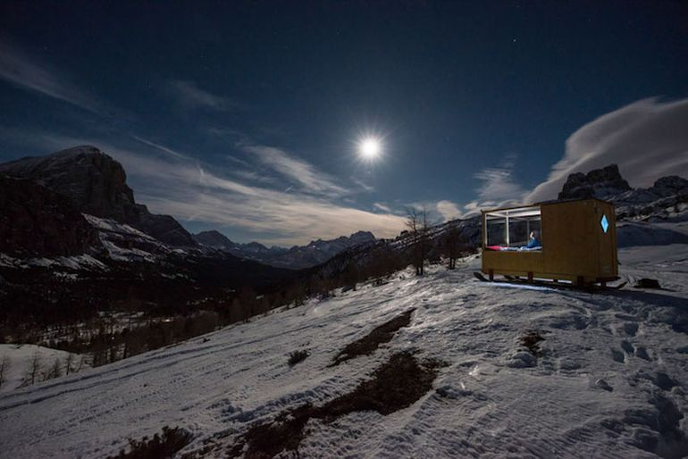 Wooden Cabin On Skis Offers Nighttime Views Of Mountains-5