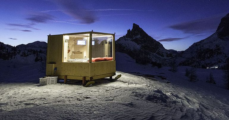 Wooden Cabin On Skis Offers Nighttime Views Of Mountains-1